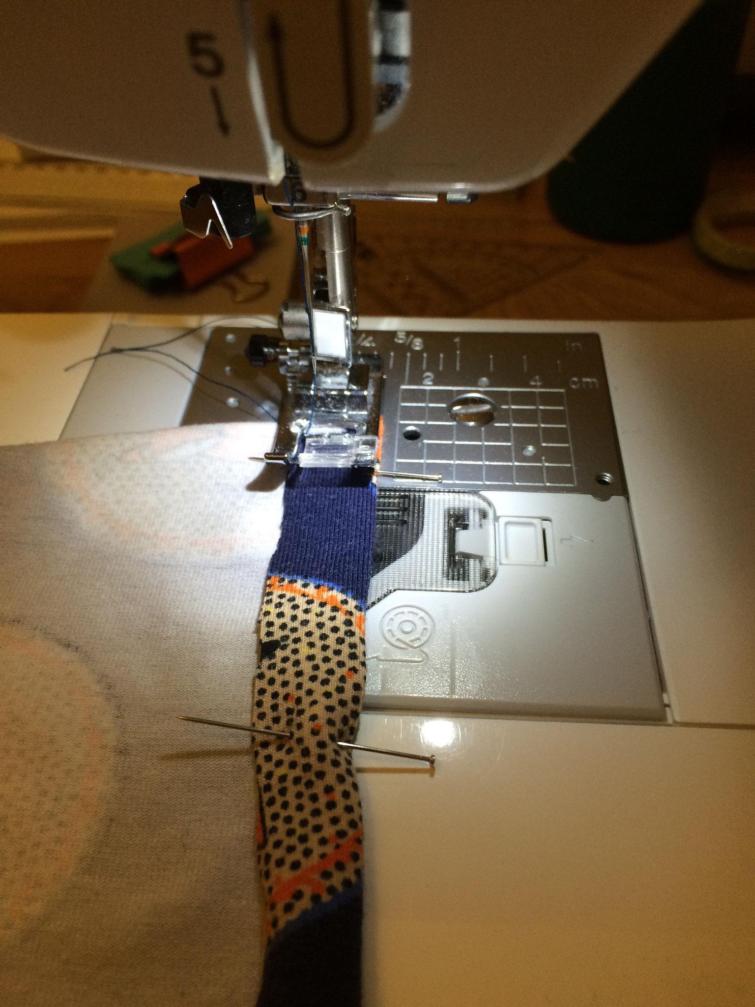 An den kurzen Seiten eures Rechtecks schlagt ihr den Stoff (bei Jersey) 1x 1cm nach innen um (bei Baumwolle 2x 1cm umklappen, damit es nicht ausfranst) und steckt dies mit Nadeln fest. Anschließend näht ihr es knappkantig fest.