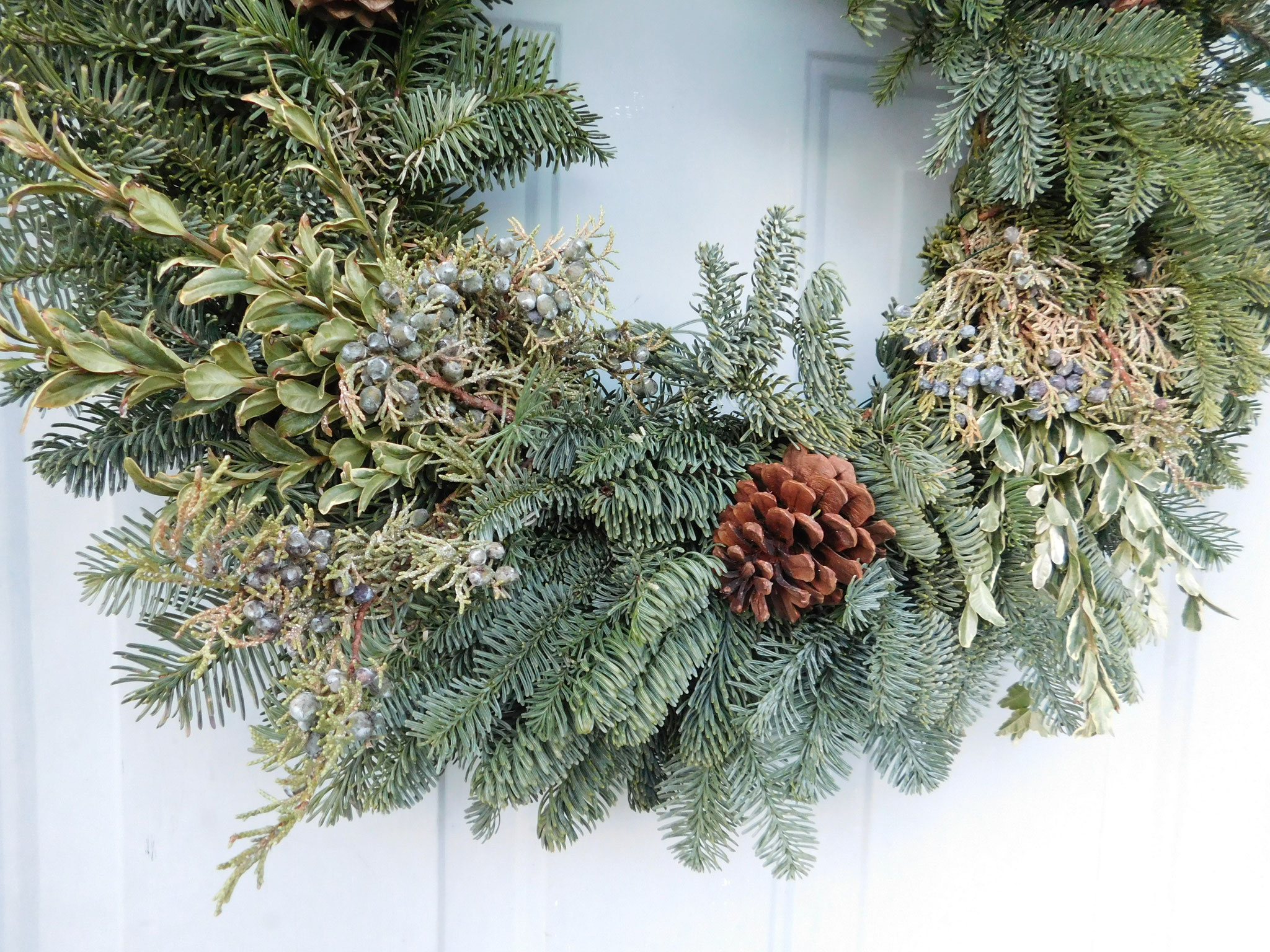 Love the berries and pine cones in our wreath!