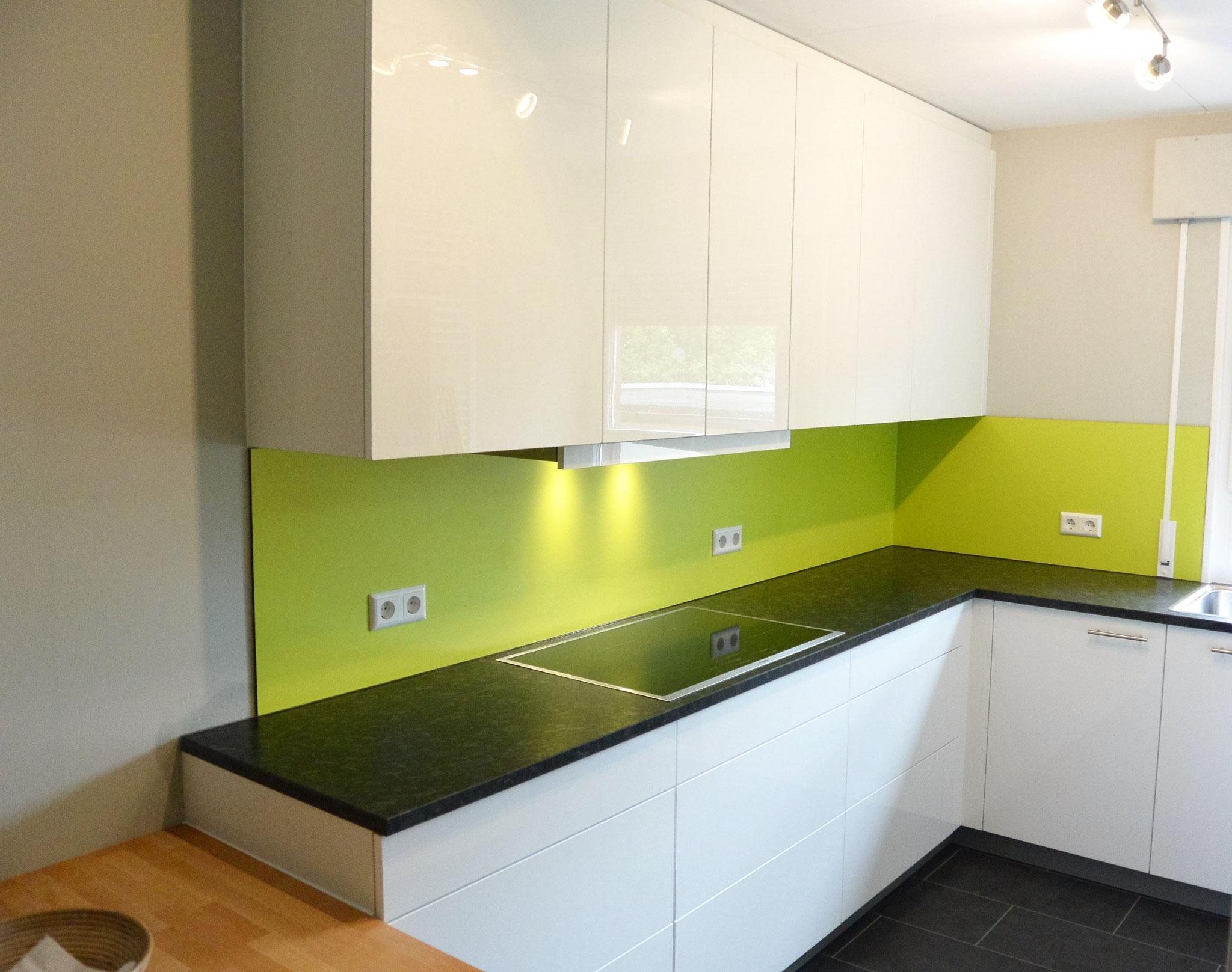 Einbauküche in Hochglanz weiß mit grünen Nischenplatten & schwarzer Granit Arbeitsplatte