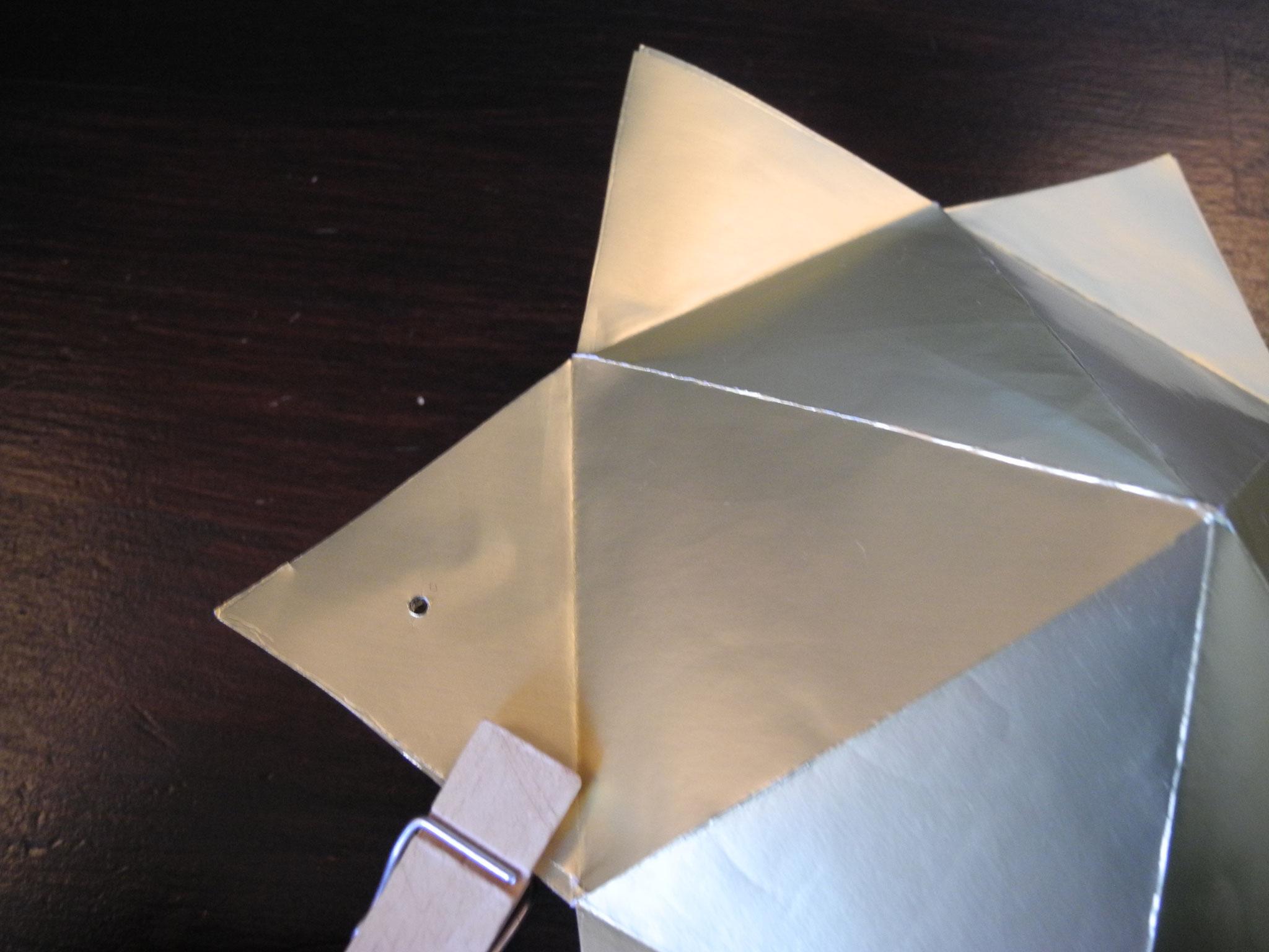 Mit der Nadel ein Loch durch die Öffnungszacke stechen und einen Faden zum aufhängen durchziehen