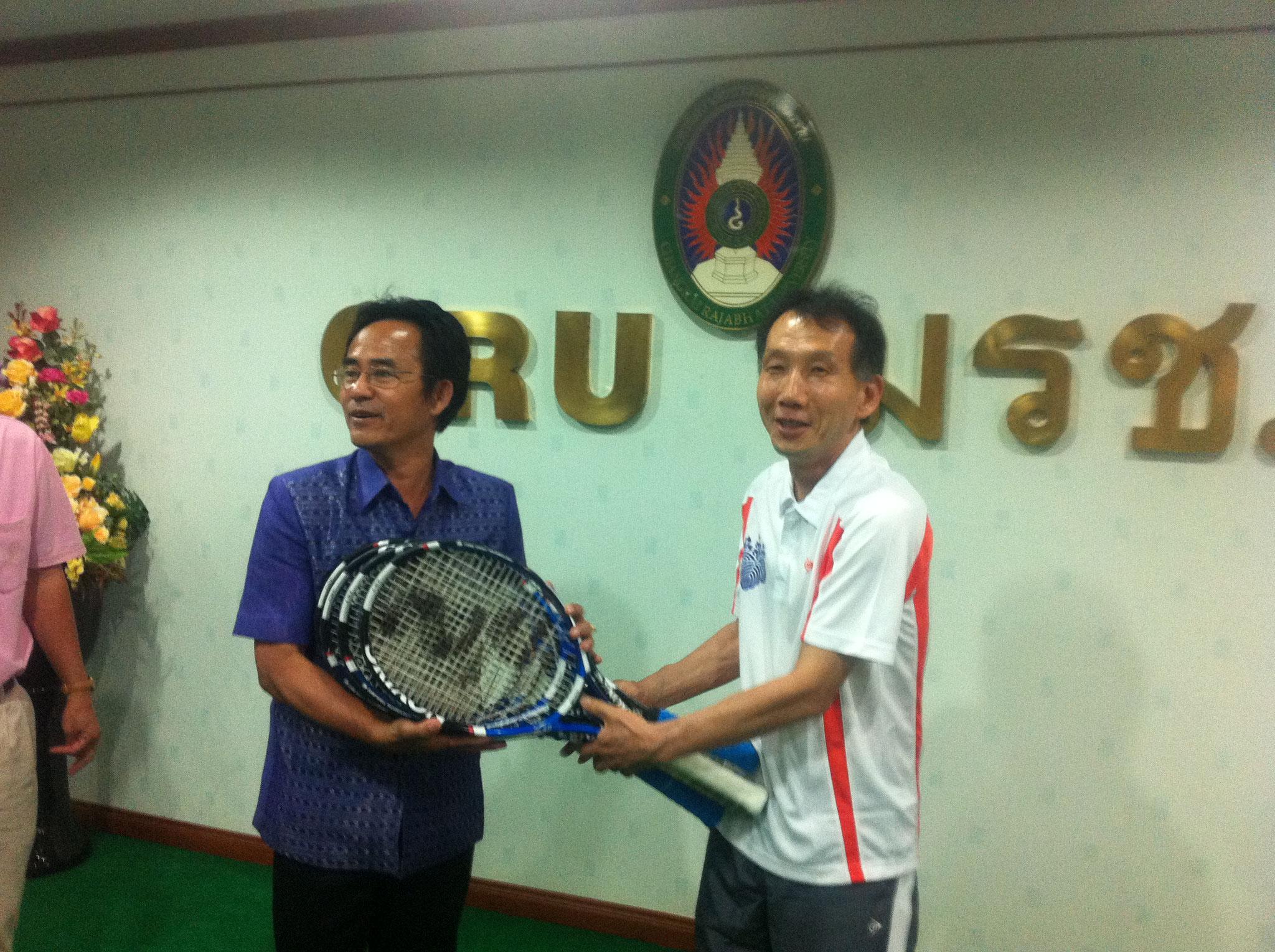 SRIスポーツよりいただいた中古ラケットを寄贈する山田先生