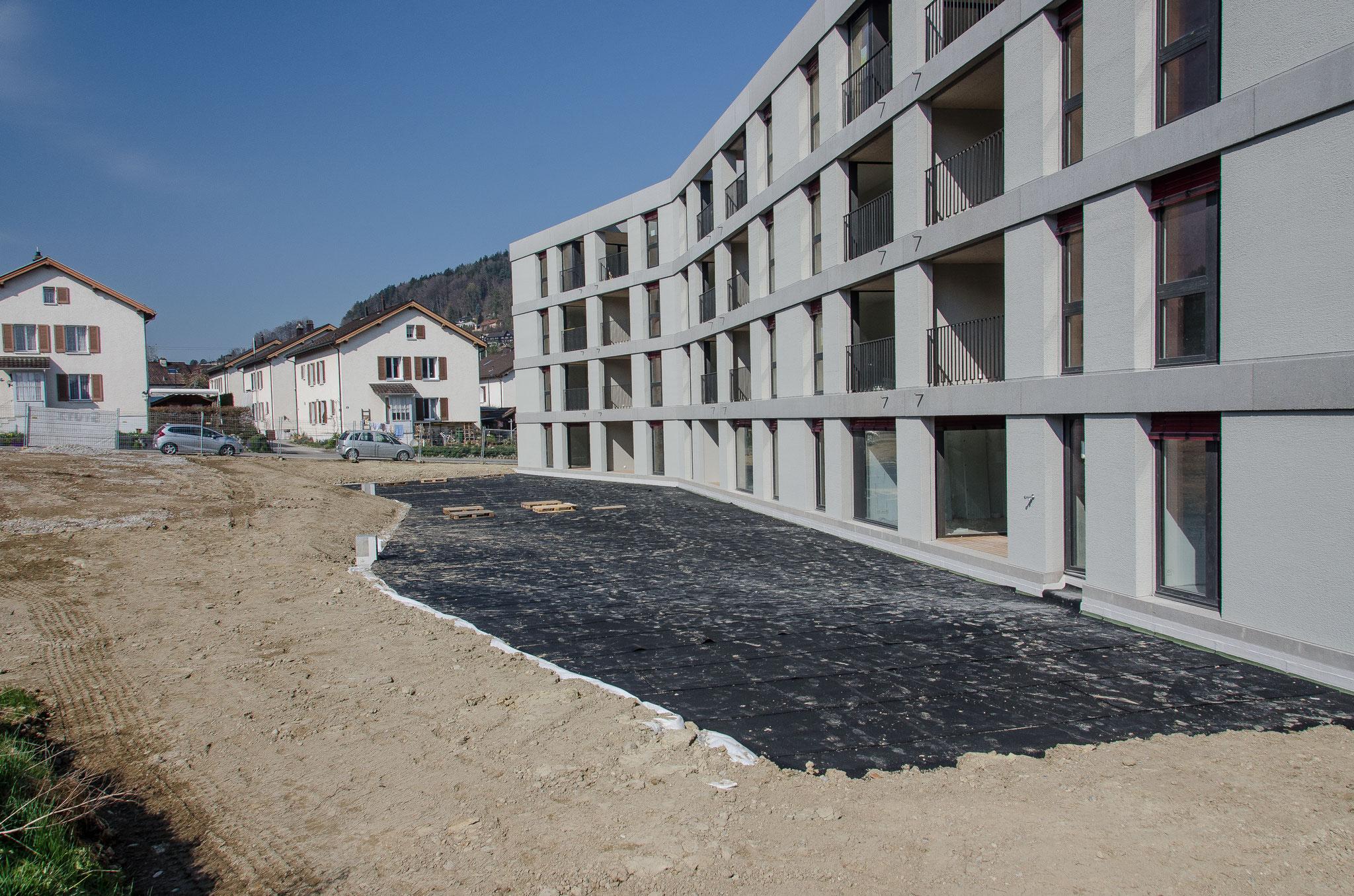 Das Dach der Tiefgarage ist abgedichtet und wird, wie die ganze Fläche südlich des Gebäudes, mit einer Humusschicht zugedeckt und bepflanzt.