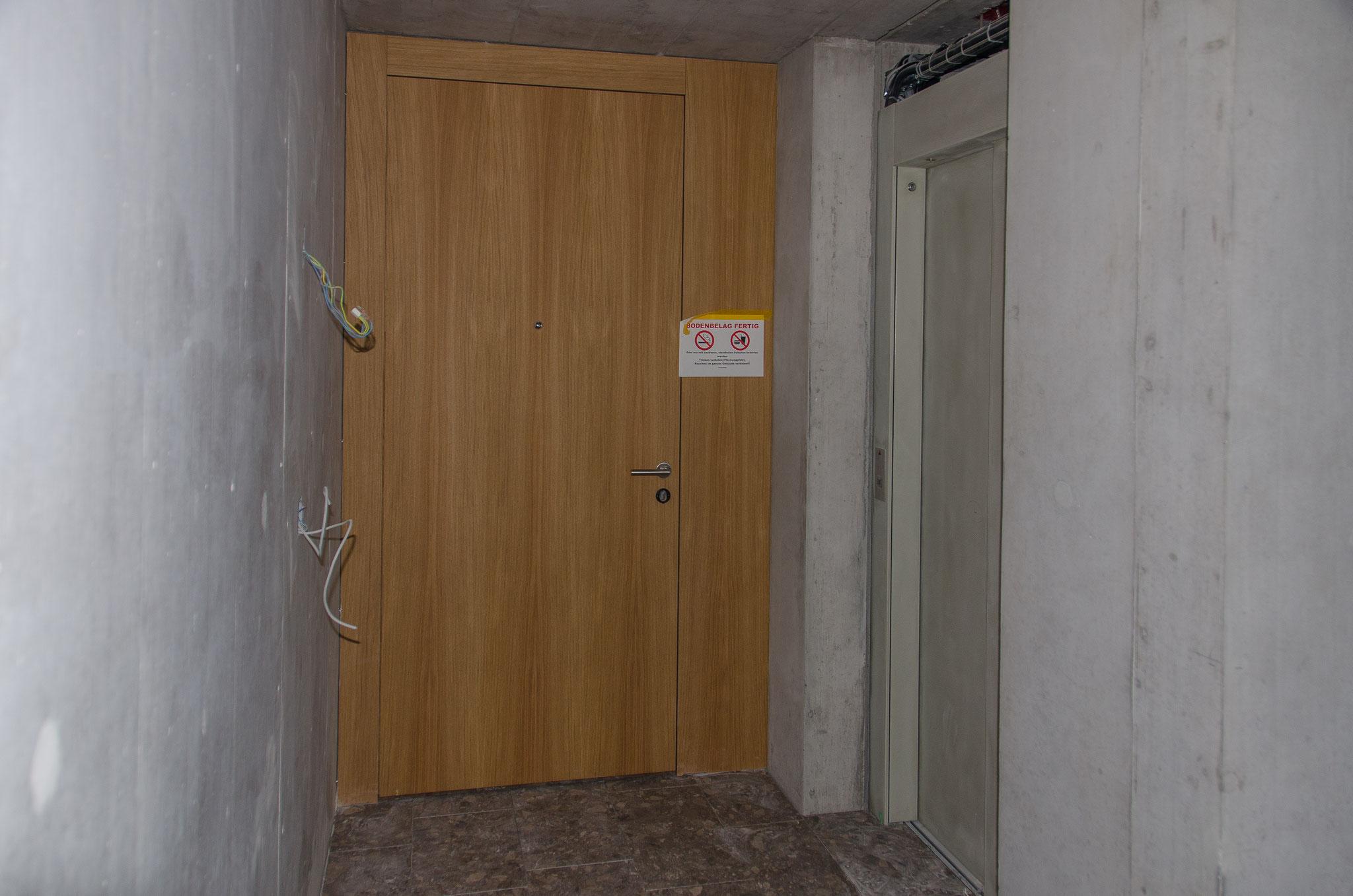 Auch der Innenbereich wird Schritt für Schritt wohnlicher. Hier eine Wohnungstüre unmittelbar neben dem Lift und Treppenhaus.