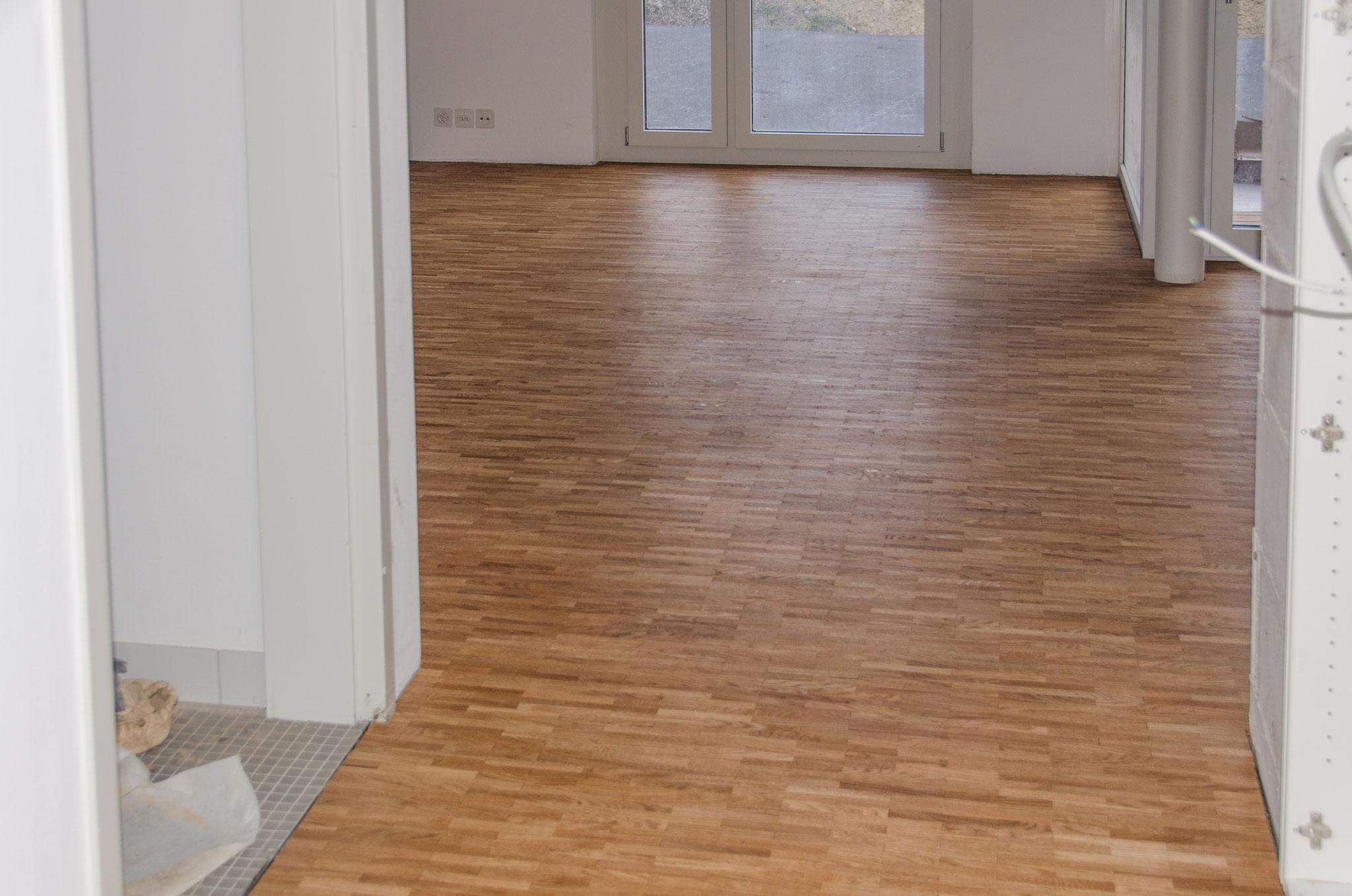 In einigen Wohnungen sind die Böden bereits geschliffen und geölt. Die Sockel werden in einem nächsten Schritt montiert.