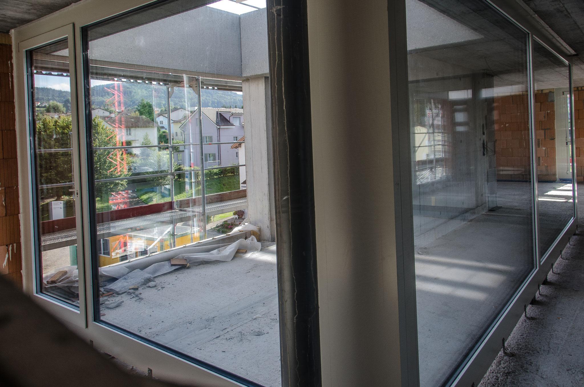 Ein Blick vom Zimmer durch die Scheiben in die Loggia und die Umgebung aus einer 4½ - Zimmerwohnung im 3. Obergeschoss.