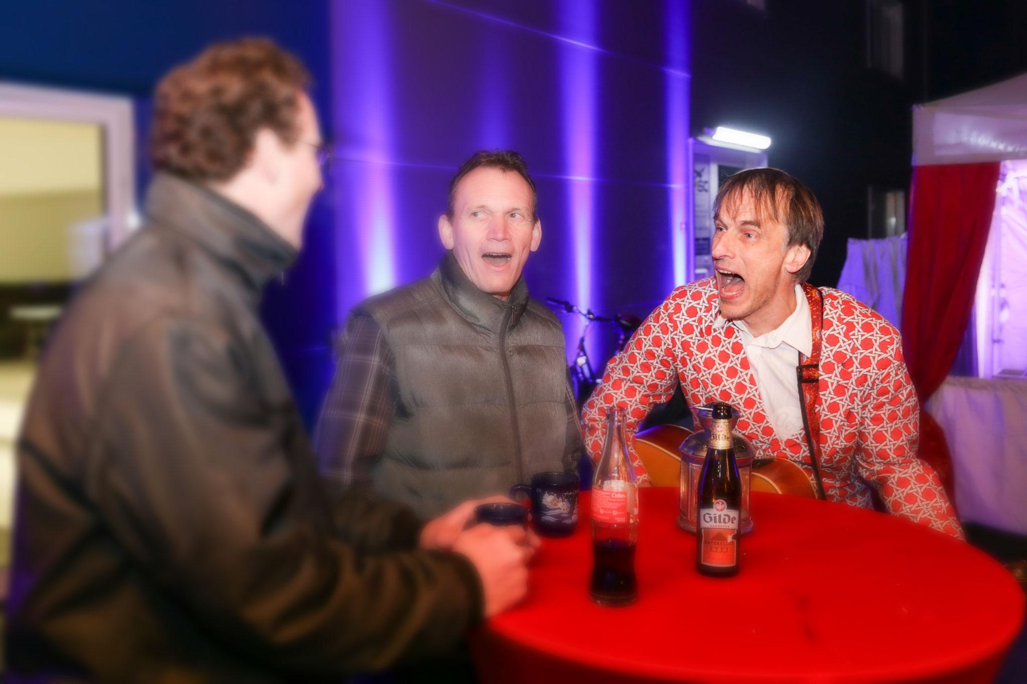 Musiker mit Gästen am Tisch, die Spaß haben