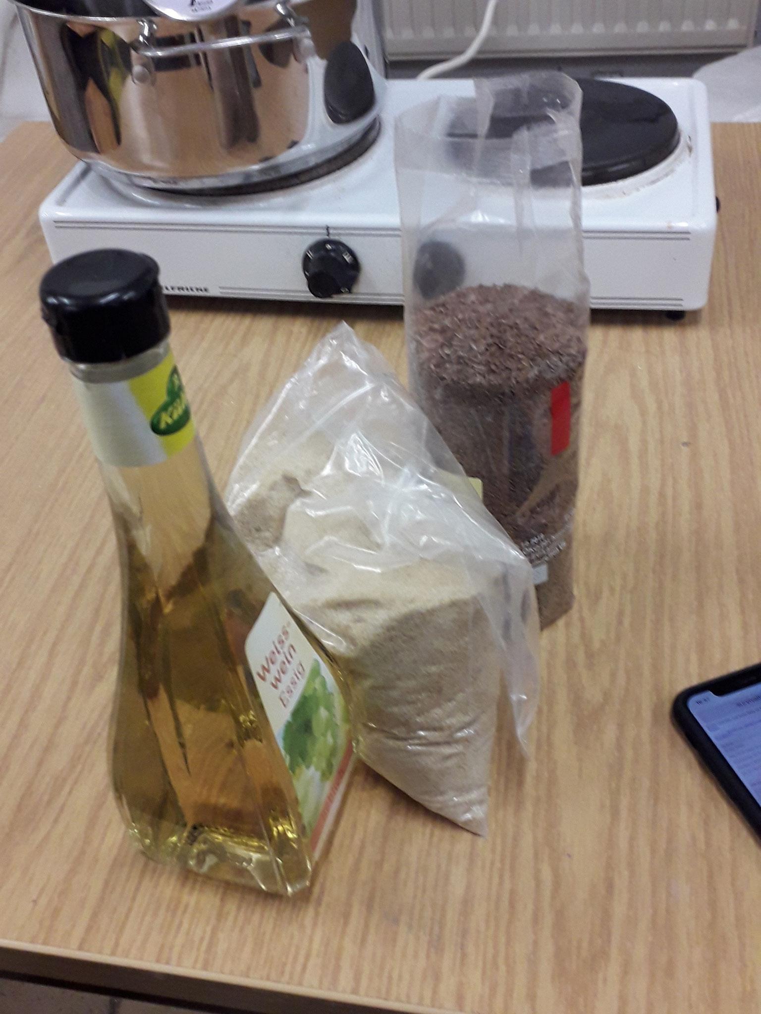 Die verwendeten Materialien für den Leim: Granulat für den Hasenleim (Mitte) und Leinsamen sowie Essig für den Leinsamenleim.