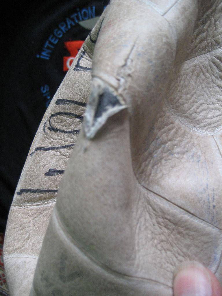 Dann schneiden wir vorsichtig ein kleines Loch mit einem scharfen Messer in das Leder.