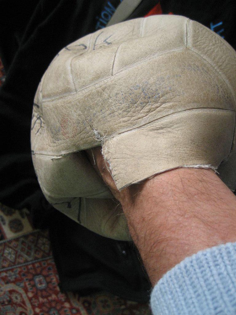 Wir greifen mit der Hand in den Lederball und ziehen vorsichtig die Blase vom Leder ab.