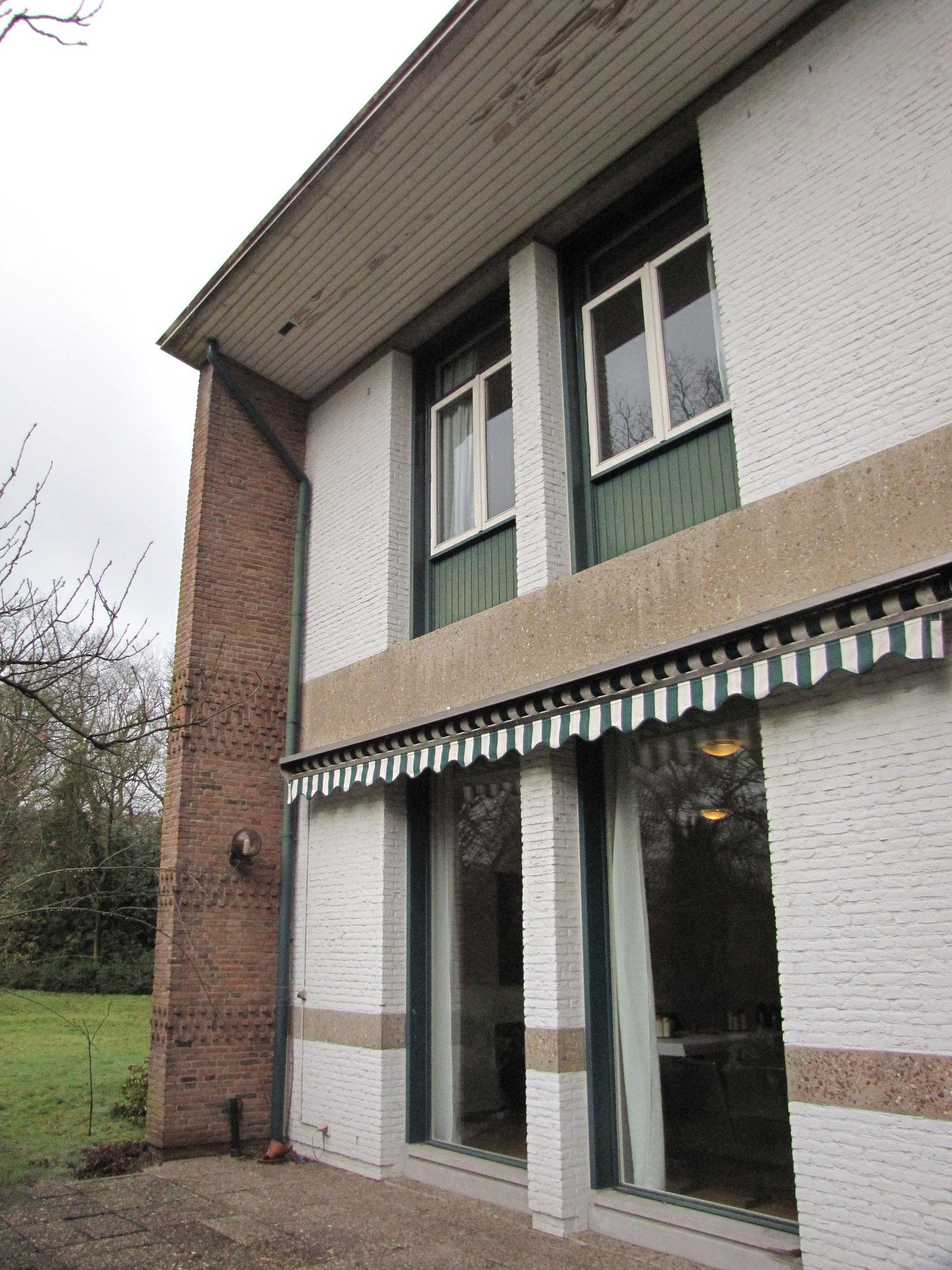 Detail van de achtergevel van het huis: rijke detaillering in metselwerk, opvallende terugliggende vensterpartijen.