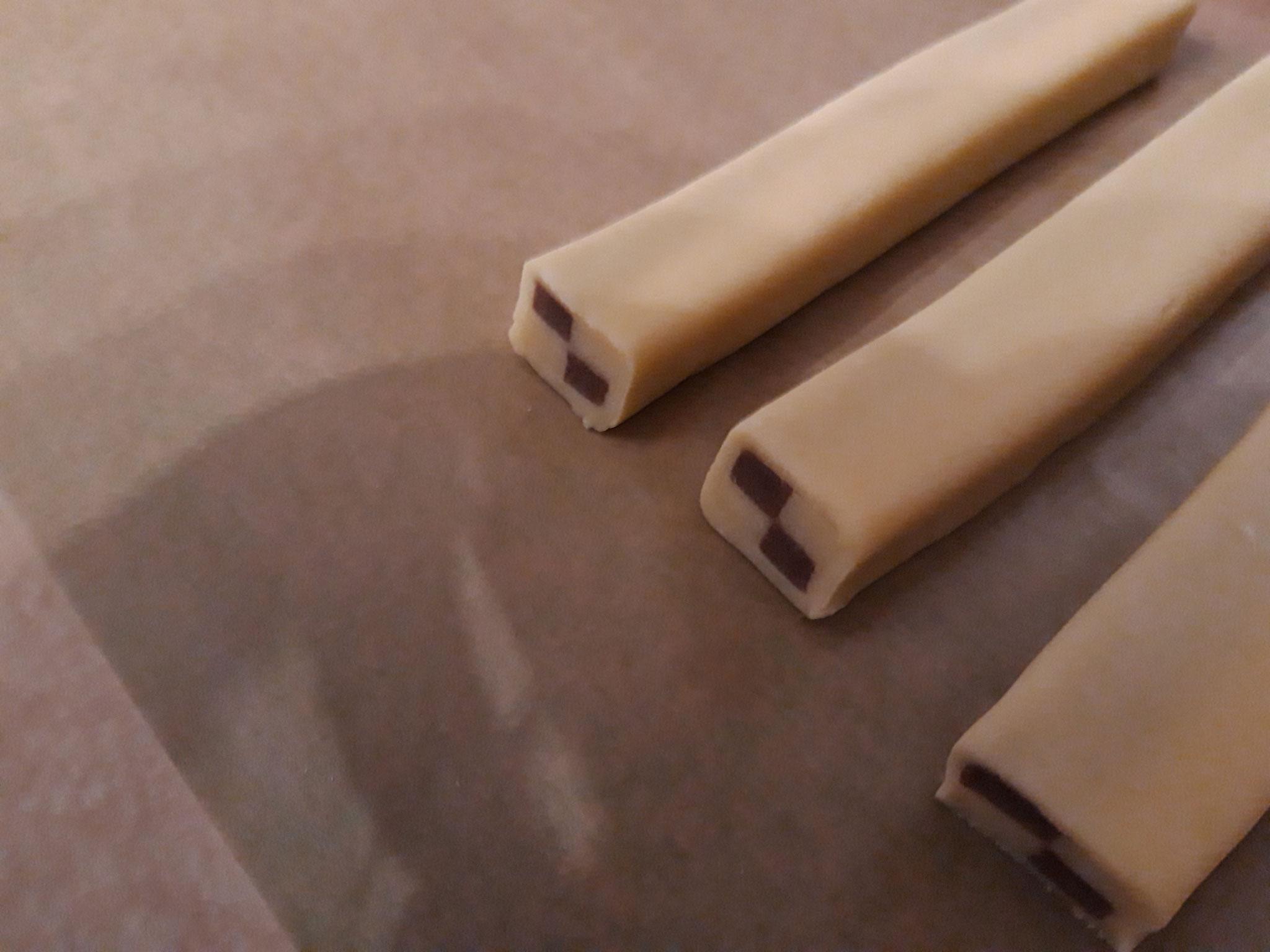 Die kleinen Blöcke mit dünn ausgerollten hellen teig einschlagen ( mit Eiweiß kleben)