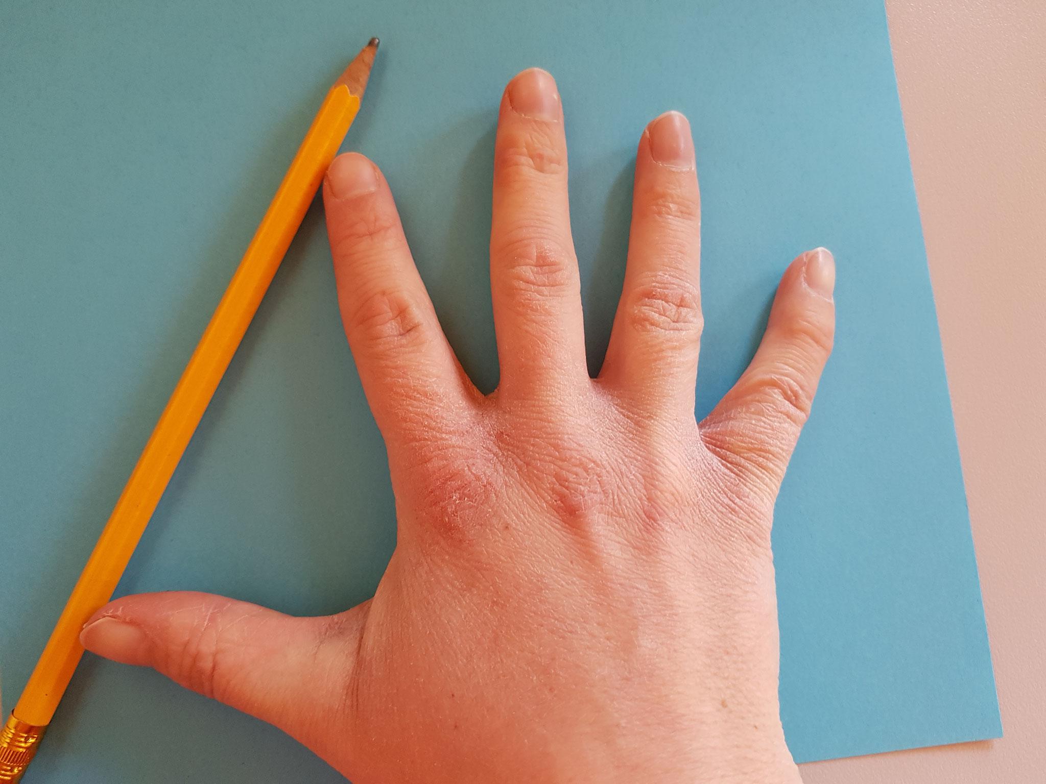 ...male deine Hand auf buntes Papier...