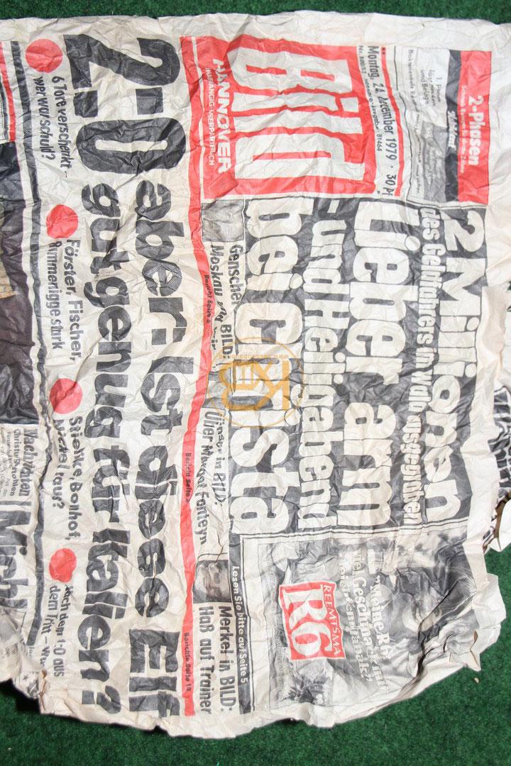 Schwarze hohe Fußballschuhe mit roten Applikationen mit genagelten Stollen aus den 1950er Jahren. In den Schuhen steckte eine Bildzeitung aus dem Jahr 1979. 2/2