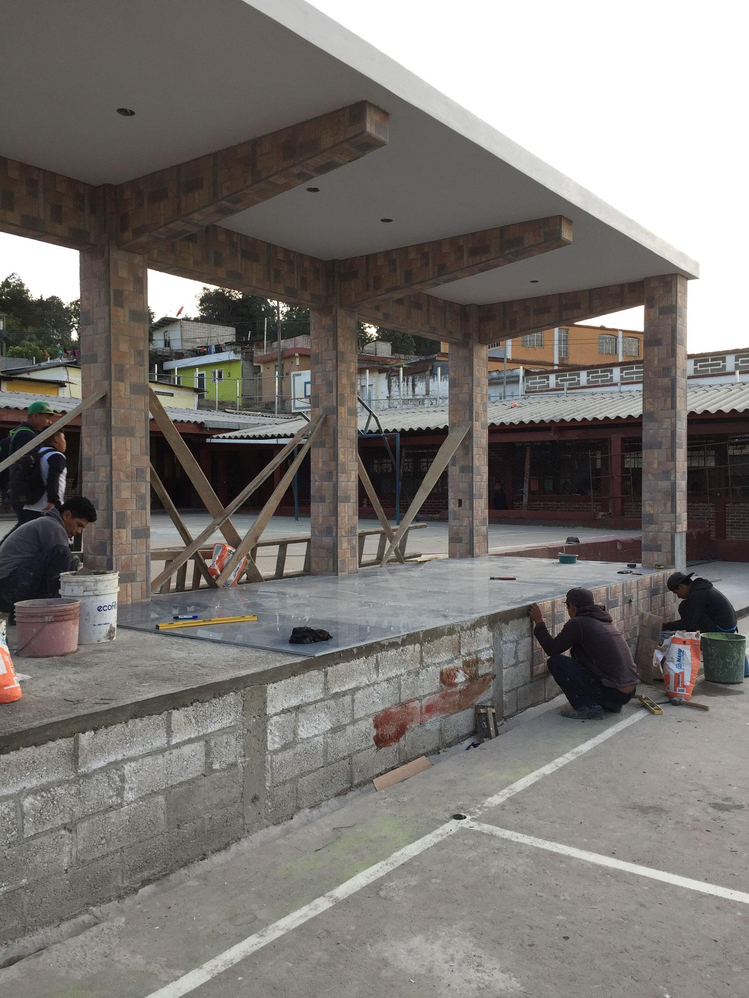 Bauarbeiter während des Neubaus einer Bühne für Schulveranstaltungen.