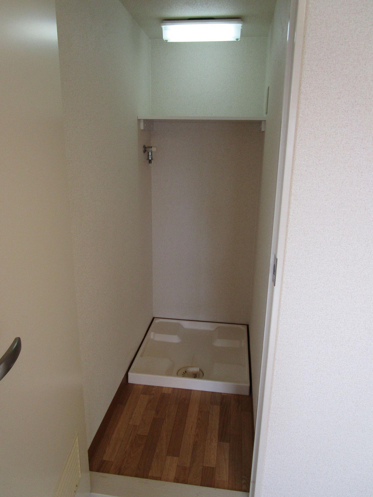 扉付きの洗濯機置場。上部に、照明と棚があります