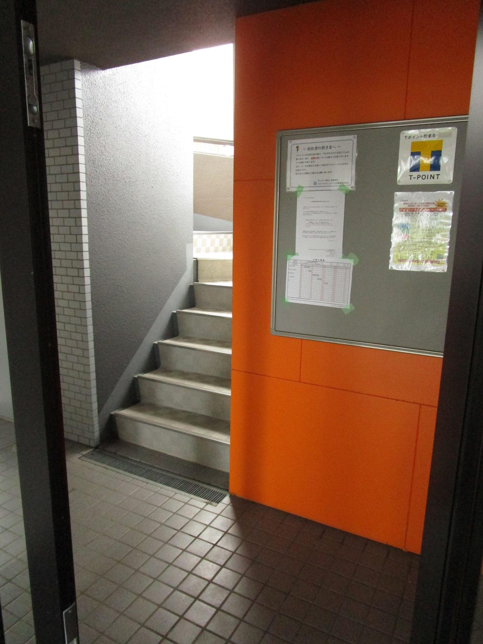 その奥の扉の向こうは、掲示板と階段