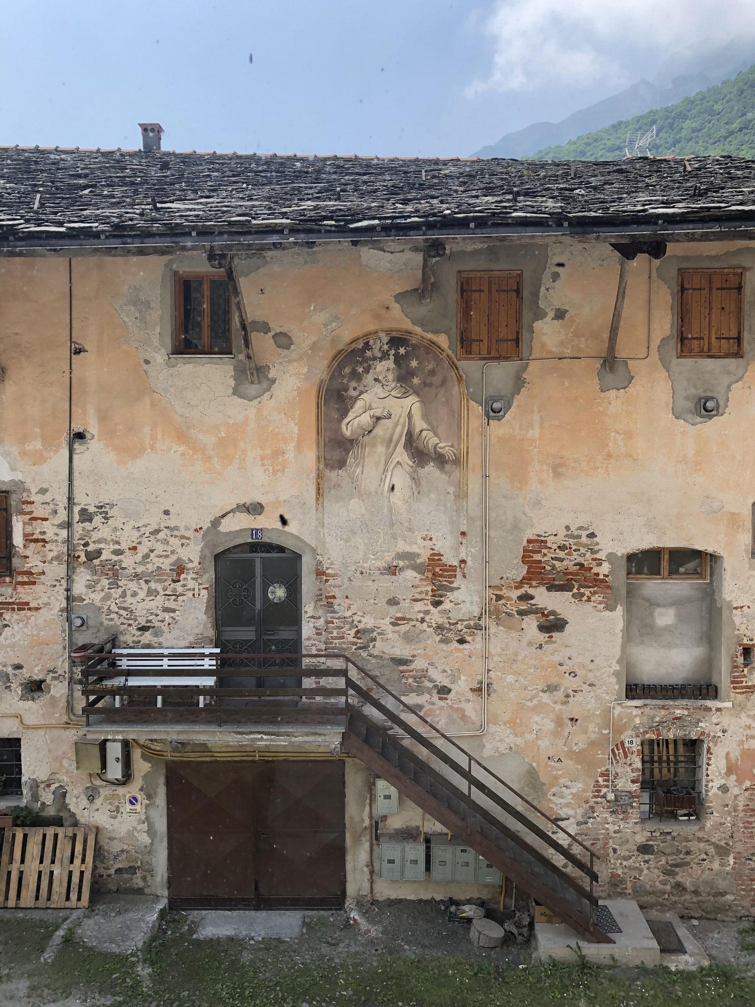 Façade non restaurée avec peinture murale.