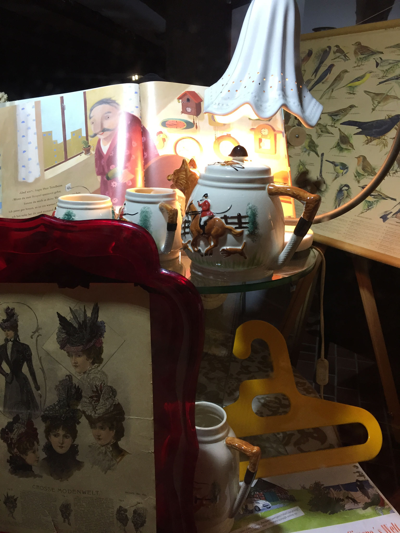 Blick in ein Stilleben-Dorfhausfenster mit Teekanne, aufgeschlagenem Buch und Vogelposter