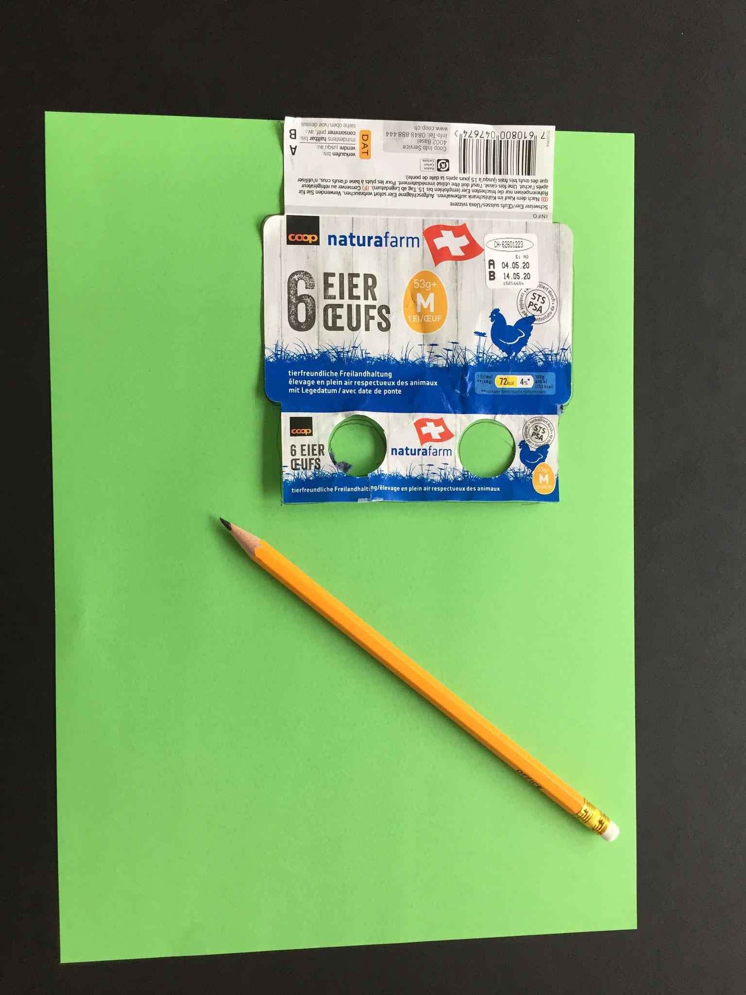 Du legst die Etikette der Eier-Schachtel auf ein Papier. Mit dem Bleistift fährst du am Rand ringsum nach.