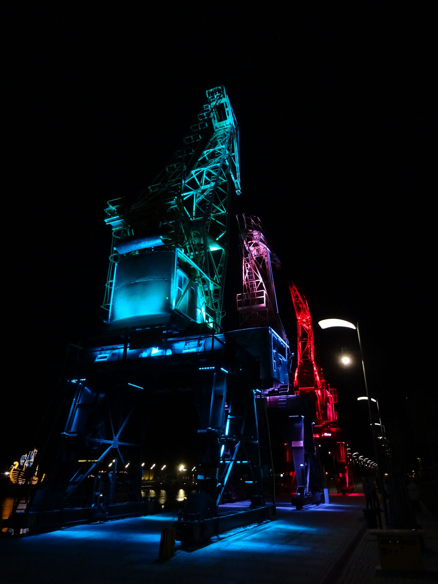 Stettin Hafen Nacht alte Krananlage Lichtinstallation blau rot pink magenta