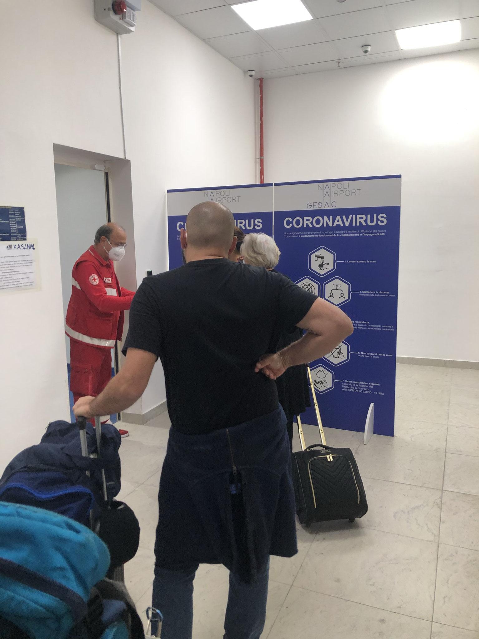 ナポリ空港:完全防護服をまとった保健所職員が部屋に待機しており、綿棒挿入によるPCR検査