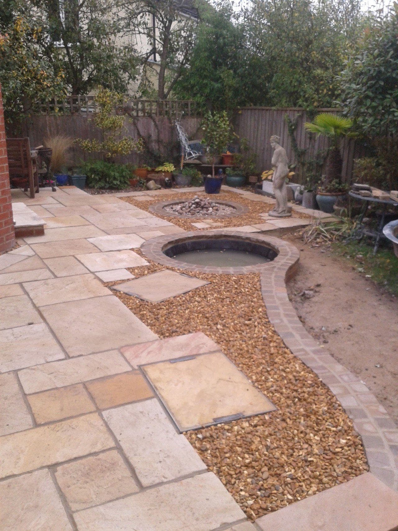 Indian stone slabs with setts  around the edge a pond and gravel