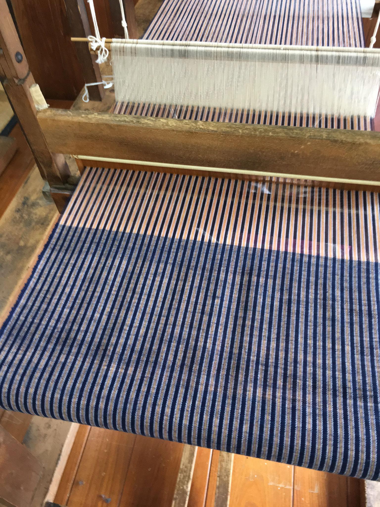 草木染めで染めた経糸を張り、緯糸には紡いだ糸を使います。
