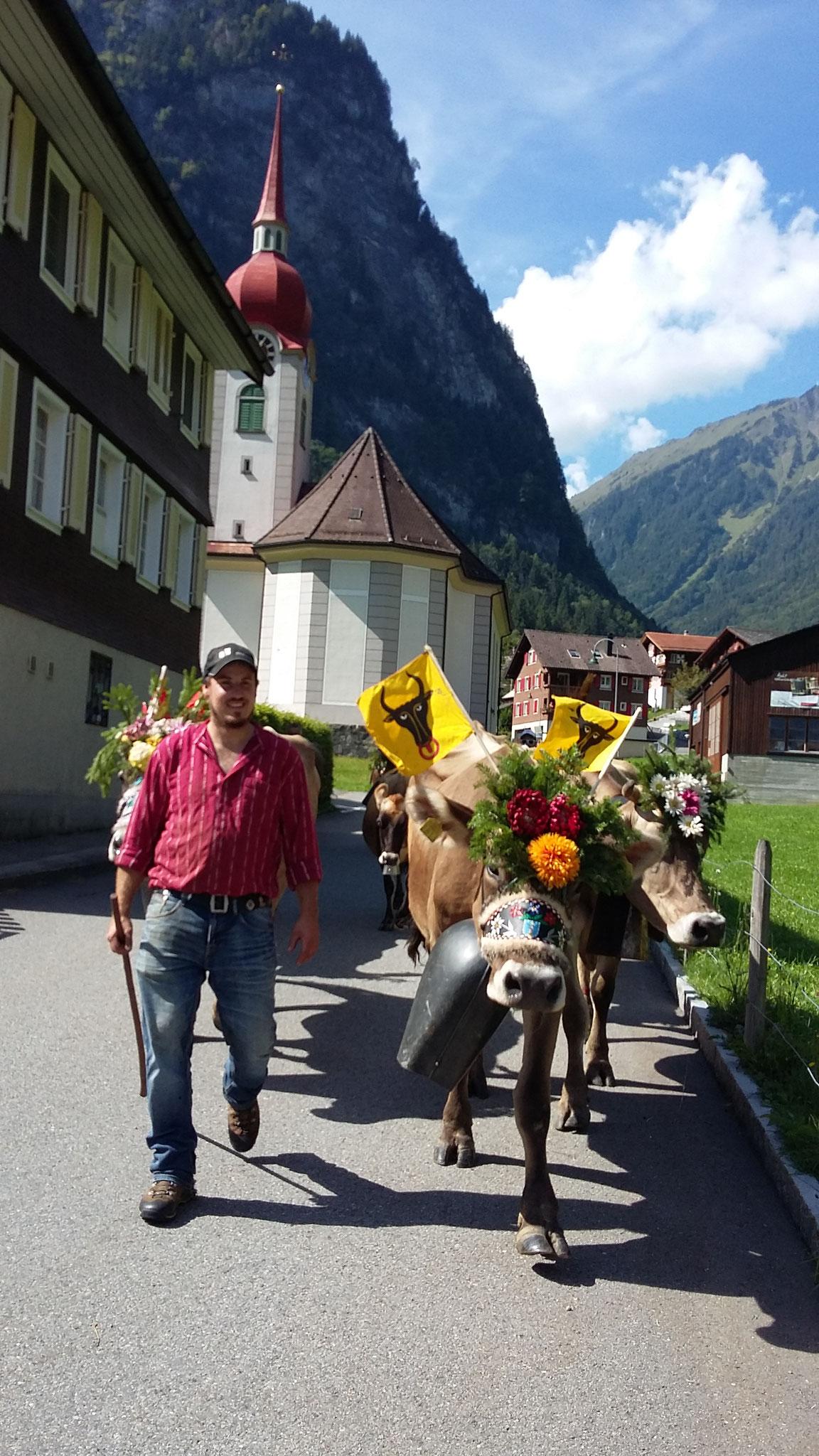 Mit Glockengeläut und Blumenschmuck ziehen wir durchs Dorf.