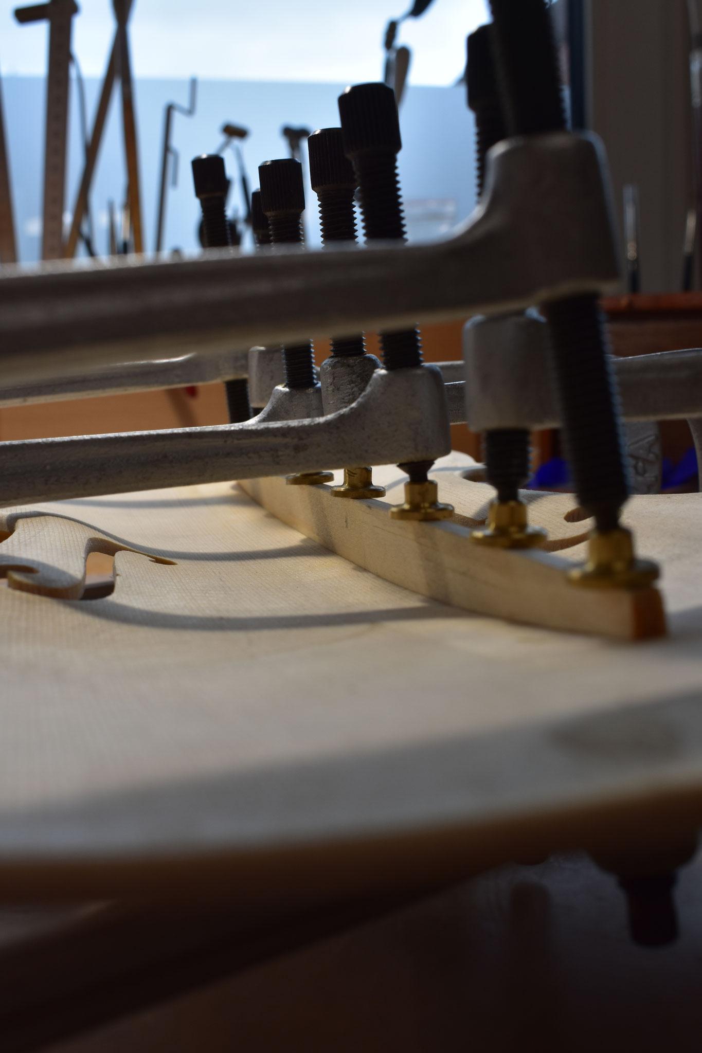 Der Bassbalken wird der Deckenwölbung angepasst und anschließend unter Spannung verleimt.