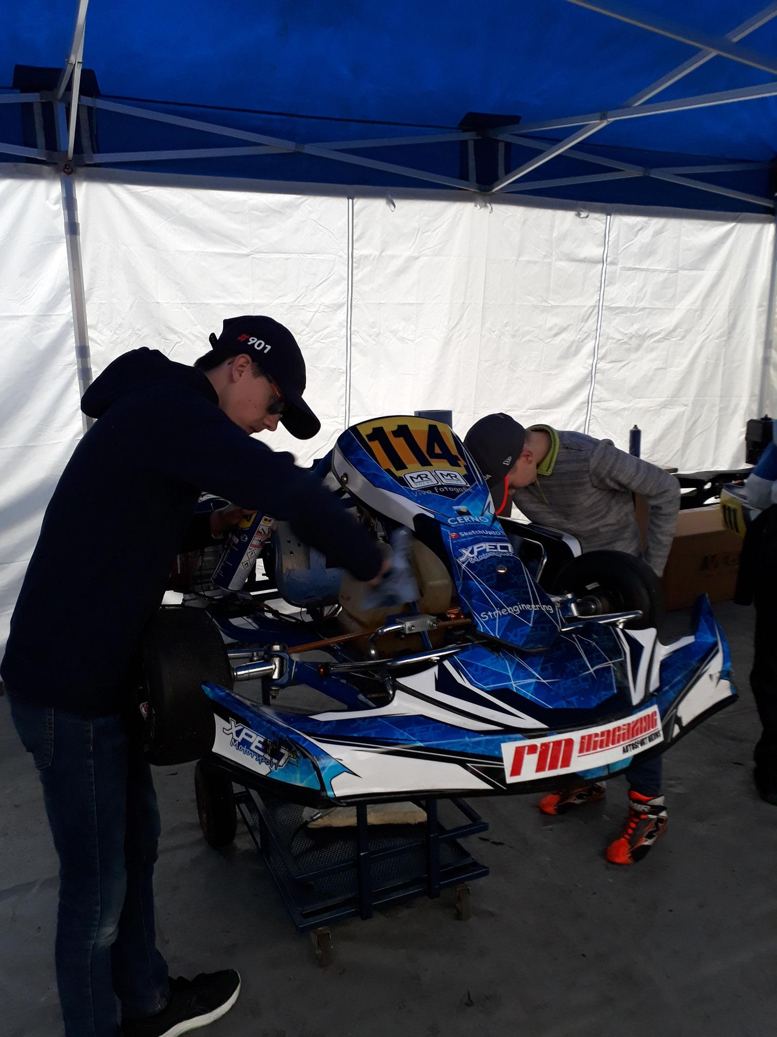 Samen met Iano zijn kartvriend in het team de kart schoon poetsen voor de race.