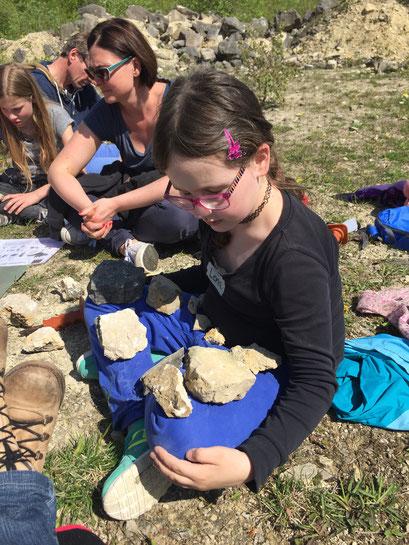 Ein Mädchen präsentiert die Fossilien