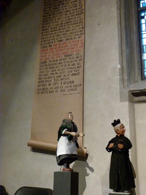 Die Wäscherin und Pfarrer Kirsch schauen auf das kleine Engelchen im Südschiff, im Hintergrund der Johannes-Prolog  (Milieukrippe Lyskirchen Foto Matthias Schnegg, Gestaltung Benjamin Marx)