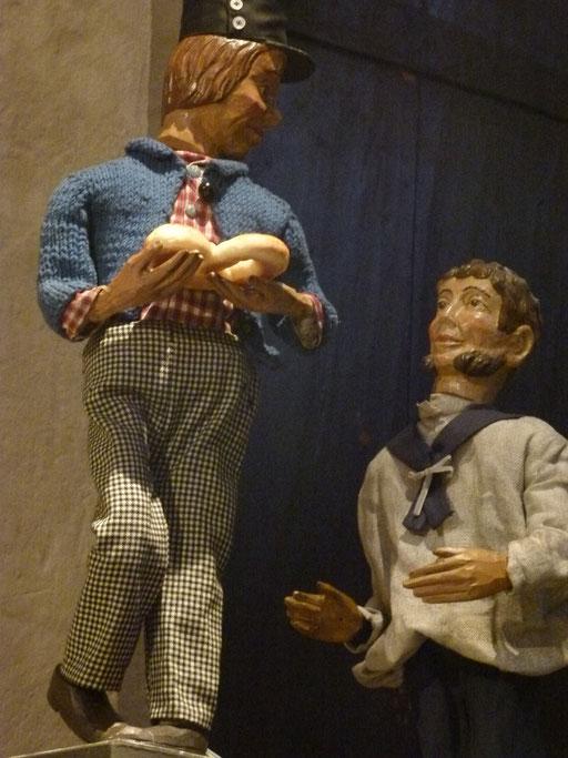 Ringroller freut sich seinem Freund, dem Matrosen eine Brezel zu schenken (Milieukrippe Sankt Maria Lyskirchen, Idee und Konzeption: Benjamin Marx, Foto: Matthias Schnegg)