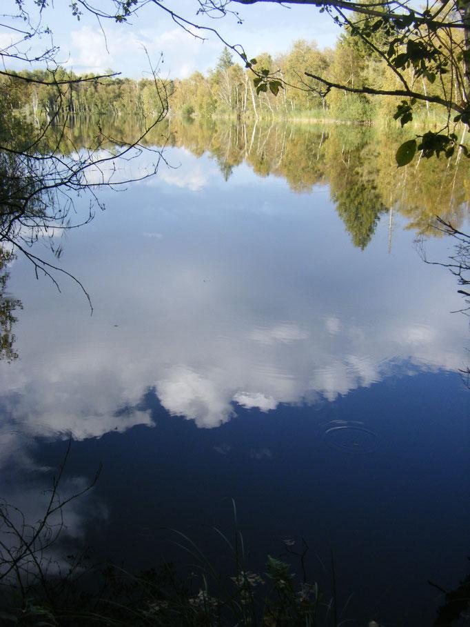 vollkommen ruhiges Wasser spiegelt den Himmel
