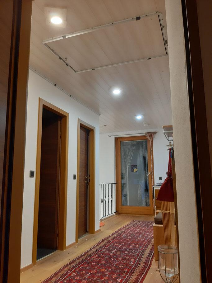 Vorraum Decke vorher mit Holzverkleidung, danach Spanndecke weiß, glänzend mit Beleuchtung; Foto:  MERLIN