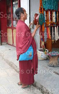 Moine tibétain faisant l'aumône avec son tambour-hochet en bois et sa clochette à foudre. Népal. © Brigitte Blot