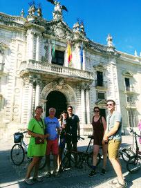 Visite guidée à Vélo en famille Séville, devant l'ancienne manufacture des Tabacs, aujourd'hui l'université de Séville.