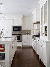 Kitchen with white Shaker-style cabinets, white quartz countertops, white walls and ceilings, and a dark brown wood floor.