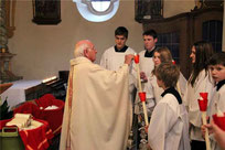 Pfarrer Raimund Arnold entzündet die Lichter der Ministranten.