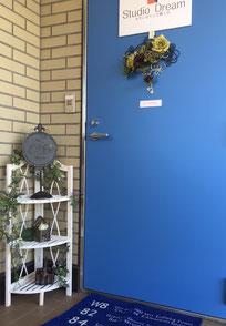 鮮やかな青の入り口にワイヤーのウェルカムプレートがかかっています