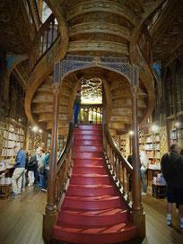 Buchhandlung Lello: Geschnitzte Holztreppe, die sich in zwei Aufgänge verzweigt und in den ersten Stock windet