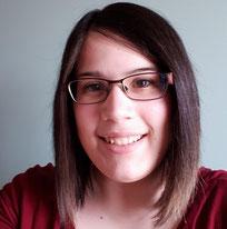 Femme souriante avec les cheveux courts bruns qui porte des lunettes pour la vue et un chandail rouge.