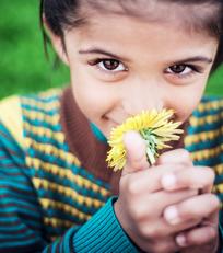 Kleines Mädchen riecht an Pflanze