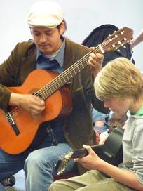 Ein erwachsener Gitarrist spielt gemeinsam mit einem Kind Gitarre.
