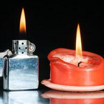 Feuerzeug und Kerze mit Flamme