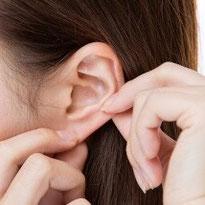 写真:自分自身で耳つぼを貼っている様子です。
