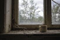 Foto von einem Fenster mit einer alten Tasse in einem verlassenen Herrenhaus