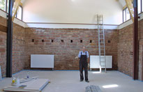Hier ist der Festsaal noch Baustelle: Der Erlenbacher Nikolai Jenicke beim Verfugen der Sandsteine in den Wänden der ehemaligen Scheune.