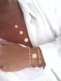 accumulation de colliers et bracelets médailles dorés