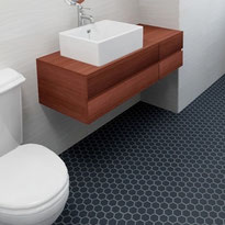 Bathroom with white walls, dark blue hexagon tiles on the floor, a floating cherry wood cabinet with a white vessel sink